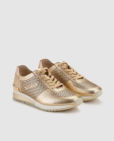 Zapatillas de piel de mujer Michael Kors de color oro con efecto metalizado. Modelo Tilda Trainer.