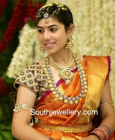 South Indian bride in stunning traditional bridal jewellery. She is adorning a short antique gold temple mango necklace and a long broad kasu haram studded with diamonds and precious stones, paired up with antique finish jhumkas, polki diamond armlet and kasulaperu vaddanam.