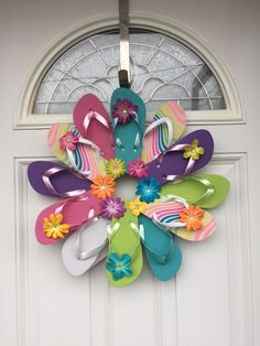 """Flip Flop Bright Sun Fun, Decorate your door or room with the summer footwear we love to wear. This wreath is fastened with greening pins making it sturdy and heat resistant. The wreath measures approximately 22"""" across, includes 12 youth flip flops and comes with a variety of flower embellishment's. Please avoid displaying this wreath in between a storm and house door. Too much direct sunlight causes extreme heat built up."""