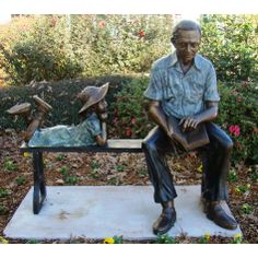 Bronze Statue of  a Man on Bench Reading a Book to a Girl