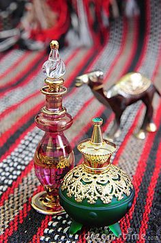 Photo about Egyptian perfume bottles arranged on a hand-woven Omani rug. A small copper replica of a camel is faded in the background. Image of cologne, omani, bottles - 5418710 Egyptian Perfume Bottles, Antique Perfume Bottles, Vintage Bottles, Bottles And Jars, Glass Bottles, Juice Bottles, Art Beauté, Egyptian Party, Genie Bottle