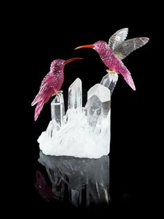 A Tourmaline Carving of Two Hummingbirds, consisting of two intricately carved pink tourmaline hummingbirds, one in flight with smoky quartz wings, the other seated, both with carnelian beaks and gold vermeil feet, the birds rest upon a rock crystal quartz cluster.