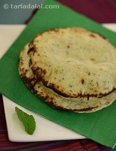 "A popular leavened bread of exquisite taste cooked in a clay oven (which is known as a ""tandoor"" and is known to have originated in persia). The tradition carries on even today in modern day iran and several north indian homes. I have added some pounded mint leaves to the naan dough to enhance the flavour and appearance of this bread. I have also made smaller sized naans so that they can be cooked faster."