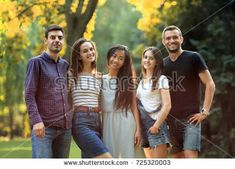 Five young people friends looking at camera in sunny park. Beautiful men and women company walking together in free weekend. Team, friendship, unity concept