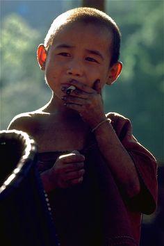 Karen hill tribe boy smoking home grown tobacco, 1980, Thailand, photograph by John Spies.