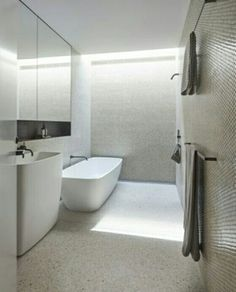 White terrazzo floors, white tile mosaic walls