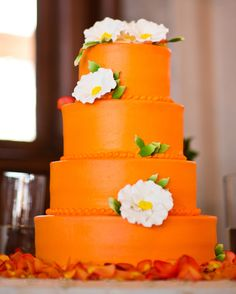 """This orange, four-tiered cake from The Mixing Bowl Bakerycontainsthree different flavors: marble cake with chocolate ganache, two tiers of lemon cake with raspberry filling, and butter cake with Bavarian cream filling. """"I've never been the girl who wanted a traditional wedding cake,"""" the bride said. """"So I decided to go with my favorite color, orange."""""""