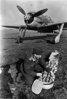 German aircraft technician prepares a cluster bomb for a fighter-bomber, the Focke-Wulf Fw 190F