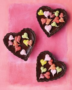 "Chocolate Ganache Heart Tartlets. ""Chocolate lovers will adore these dark, rich tartlets. The silky bittersweet-chocolate filling provides a sleek backdrop for a rainbow of piped meringue hearts. Make a large version for a party or minis like these, each sized for two to share."""