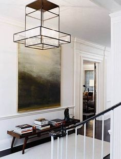 fabulous light fixture and overscale painting make for a simple yet dramatic foyer