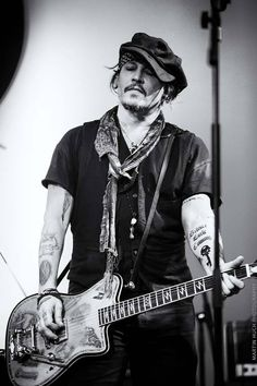 Johnny Depp rocking on guitar, The style of depp with his tattoos makes effect and looks good.
