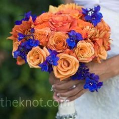 Coral and Blue Wedding Bouquet Amazing Blue delphiniums popped against three types of orange roses. For extra glamour, the stems were wrapped in satin adorned with rhinestones. Orange Wedding Flowers, Orange Flowers, Flower Bouquet Wedding, Wedding Colors, Flower Bouquets, Bridesmaid Bouquet, Yellow Roses, Bridal Bouquets, Bear Wedding