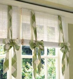 Slice up a inexpensive bamboo blind and glue the strings in place to prevent unraveling. Next, staple one edge to a narrow board; secure this to the top of the window. Roll several inches of the blind around a thick dowel and hold up with pretty fabric bands.
