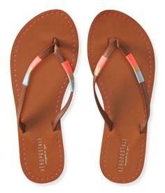 An island vacay may not be in your near future, but trendy warm-weather style definitely is! Our Perf Accent Flip-Flop features cool triangle perforations at the faux leather footbed, while bright, shimmery thread highlights the strap for serious swag under the sun.<br><br>Style: 7936. Imported.<br><br>Man-made materials.