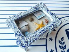 Nautical coffee table with a drawer full of nautical items (can not be open).  Handmade miniature  Measures 6.5cm long, 5cm wide and 4.6cm high (1cm: