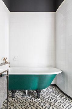 Emerald bathtub + patterned monochrome tile + brass water fixtures = vaguely Moroccan bath house.