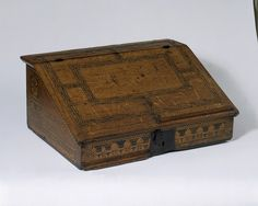 The writing desk developed in England at the end of the 16th century. Easily portable, it would be placed on a table and the writer or reader would stand in front of it. The interior of this example was originally fitted with a nest of eight drawers (four are now missing). These would have been used to store pens, paper and other writing materials. A moulded ledge on the desk lid prevented books and paper from slipping