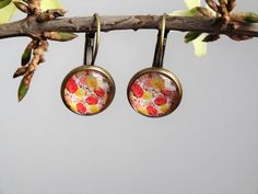 Ręcznie wykonane kolczyki z grafiką przedstawiającą drobne kwiatki w kolorystyce żółto-czerwonej. Grafika ma bardzo ładne, nasycone barwy. Przykrywające ją wypukłe szklane oczko daje złudzenie trójwymiaru.  Kolczyki z biglami angielskimi w kolorze antycznego brązu. Średnica elementu dekoracyjnego