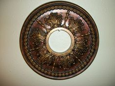 """This is a [new] hand painted ceiling medallion in tones of bronze, antique copper, and antique gold. It measures [almost] 14 """" (inches) across, and the center opening is about 3 7/8"""" in diameter."""