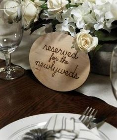"""This rustic sign is a unique addition to your outdoor wedding reception décor. The Wood Sign – """"Reserved For The Newlyweds"""" is scripted in handwritten cursive and burned into the wood. Display this natural sign by draping it over the edge of your sweetheart table"""