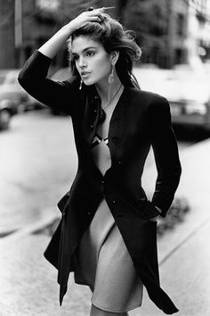 Cindy Crawford, wearing a fitted black wool coat over a striped silk slip-dress, by Gianni Versace.