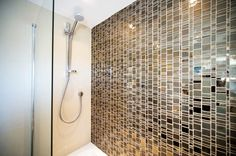 This bathroom shower has a glass mosaic called Liberty Bronzite. This color also comes in two other shapes and colors.