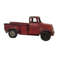 A charming vintage red metal toy truck that's obviously been a well-loved favorite. It's perfect as a decorative piece for a child's room or playroom.
