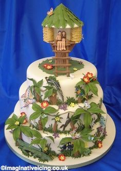 Tropical Treehouse    Round cakes stacked together. Tropical animals, trees and flowers in relief and modelled, covering the front half of the cakes. The back has been left plain, but the design can go all round the cakes at an extra cost. The treehouse is a sugar model and the figures can be made to represent the bride and groom.