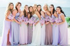 Mismatched lavender bridesmaid dresses, boho accessories for bare feet and purple flower bouquets for the bridal party at a beach wedding.