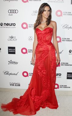 2015: Alessandra Ambrosio wore a red Atelier Versace strapless gown with a sweetheart neckline. Alessandra always looks glamorous on the red carpet. Versace is perfect for her because the creations hug her body to perfection. I love the detailing on the gown.