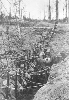 French soldiers line up for inspection in a trench strung with barbed wire. Original Publication: L'Illustration, 1916 (Getty Images).