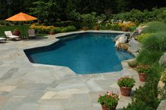 This flagstone patio centers on an angular, oblong-shaped pool, surrounded by lush greenery and large stones on one side.