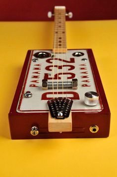 "Panama Red 4-string LP resonator.  Padron 7000 cigar box, Panama license plate. Maple neck w/ mahogany peg head: maple fret board with sapele dots. Bone nut. Dual piezo/veneer sandwich attached to neck under bridge. 25"" fret scale."