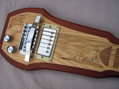 Lap steel guitar of mahogany inlaid with ash and oak fret markings, paua shell position markers and pyrographed detailing.