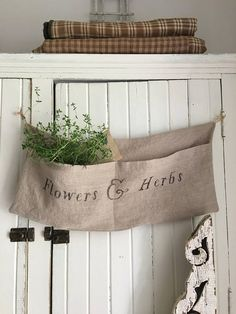 Pretty spring pocket made from natural linen...I have added the lettering and loops to hang. Measures 22x 10...Tuck in some fresh herbs or dried flowers. Ill include a vintage card copy to tuck in. Perfect hung on a cupboard door or peg rack... Thank you for browsing