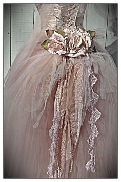 Clothing: Gown with laced back and roses bustle, beads, ribbons, and lace.