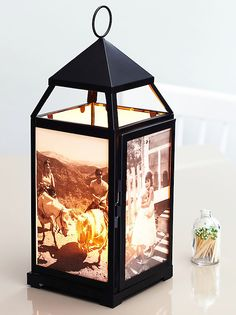 Illuminating Photo Album~ lanterns turned into glowing photo albums for the tables. Print in black and white. Trim to fit and slide the photos against the glass so images face out, tape in place. Use a battery-operated candle
