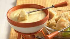 Swiss & White Wine Fondue -- 1 loaf (1 lb) French bread, cut into 1-inch pieces, 2 cups shredded Swiss cheese (8 oz), 2 cups shredded Gruyère or Swiss cheese (8 oz), *2 tablespoons all-purpose flour, 1 clove garlic, cut in half, 1 cup dry white wine or nonalcoholic white wine, 1 tablespoon lemon juice, 3 tablespoons kirsch/dry sherry/ brandy, and apple and pear slices. In resealable plastic food-storage bag, place cheeses and flour. Shake until cheese is coated with flour.  Rub garlic on bottom and side of fondue pot, heavy saucepan or skillet; discard garlic. Add wine. Heat over simmer setting on fondue pot or over low heat just until bubbles rise to surface (do not boil). Stir in lemon juice.  Gradually add cheese mixture, about 1/2 cup at a time, stirring constantly with wire whisk over low heat, until melted. Stir in kirsch.  Keep warm over simmer setting. If prepared in saucepan or skillet, pour into a fondue pot or heatproof serving bowl and keep warm over low heat. Fondue must be served over heat to maintain its smooth, creamy texture.  Spear bread and fruit with fondue forks; dip and swirl in fondue with stirring motion. If fondue becomes too thick, stir in 1/4 to 1/2 cup heated wine.