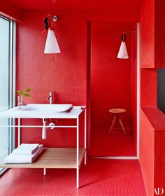 Bisazza tile lines a bath in a São Paulo home designed by the Campana brothers; the light fixtures are by Konstantin Grcic for Flos, and the vanity, sink, and fittings are by Antonio Lupi.