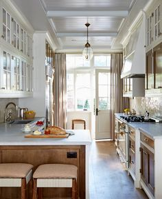 Traditional details shine in smaller spaces, too. Take this galley kitchen in Toronto designer Silvana D'addazio's own 1880s semi; the coffered, panelled ceiling is a classic move scaled down for the space, while the contrast between glass-paned uppers and walnut-panelled lower cabinets lends an elegant and tailored feel to the room. Palissandro marble counters and a Moroccan-tile backsplash are luxe additions, while a pretty pendant light feels like jewelry overhead.
