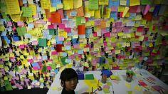 AVRIL 2014 - À Ansan, une petite fille ajoute un mot sur un mur recouvert de messages et de prières adressés aux victimes du naufrage du ferry «Sewol», en Corée du Sud. Les autorités sont toujours, jeudi 24 avril, à la recherche des corps de plus de 100 passagers, parmi lesquels de très nombreux lycéens.