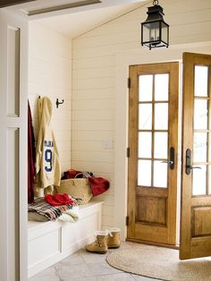 Entry/Mudroom: white planked walls, french doors, lanter, built-in storage bench, tile floors.