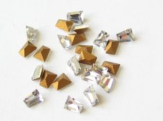 24 Swarovski tapered baguette crystal rhinestones with gold foil. 3mm long.