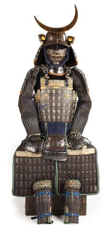 A suit of armor with a russet-iron mogami do Edo period (18th century) Laced in white and black with blue and orange highlights and comprising an eighteen-plate russet-iron sujji kabuto surmounted with three-stage tehen kanamono and fitted with a five-lame close-fitting shikoro ending in fukigaeshi trimmed in gilt-copper fukurin and applied with circular gilt-copper heraldic crests on a black-leather ground, the maedate a large gold-lacquer crescent moon;
