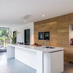 De moderne houten maatwerk keuken is niet alleen op maat en functioneel, maar heeft ook nog eens een warme uitstraling.