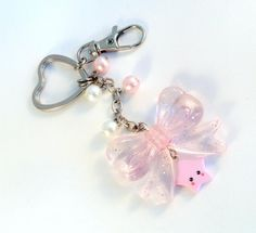 This is a cute sparkly pink bow keychain with a kawaii star, and pink and white glass pearls. It comes on a heart shaped keychain, with a clip. The clip is really convenient for clipping on your purse so you don't lose your keys. :P It's adorable! :) The star is handmade with polymer clay.   Not for children under 5.  Check out more of my jewelry and accessories here- http://www.zibbet.com/aLilBitOfCute  ***MY TURNAROUND TIME right now is approximately 3 to 5 business ...