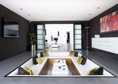 Japanese style sunken seating room/games room has fully retractable doors which open up to  the rear garden,