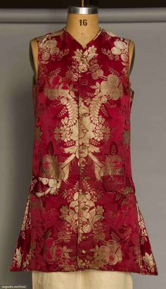 """Silk lampas waistcoat, French, 1700-1725; Deep red ground with fruit, flowers and foliage in ivory, two flap pockets, 13 of 14 self covered buttons, homespun linen tie back, replaced muslin front lining, CH 40"""", CF L 33"""", CB L 22"""""""