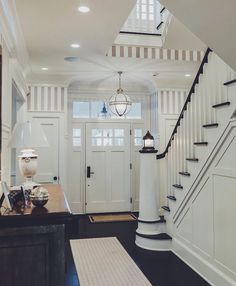 stunning entryway with a craftsman coastal traditional style. Dark wood and thick white trim.