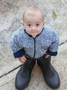 An interesting photo of cute kid wear a big shoes